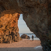 A woman walks under a natural bridge carved from colorful sandstone at Panther Beach, north of Santa Cruz, California.