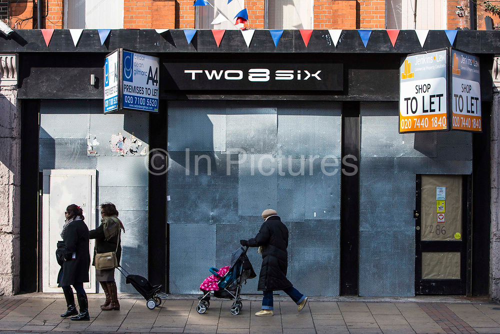 A woman with a push-chair walks past a derelict high-street shop, Lewisham, London, United Kingdom.  Many retail stores have closed down during the financial slow-down in Britain.