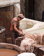 Man scraping hide in centuries-old tannery, Fez, Morocco