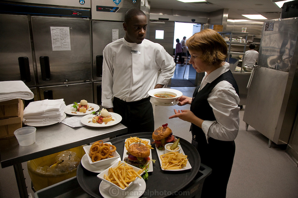 Waitstaff prepare meals for patrons at the world's highest revolving restaurant, located at the CN Tower in Toronto, Canada. The award-winning restaurant has awe-inspiring views and, for a tourist destination, surprisingly excellent food. The pricey entrance and elevator fee of about $25 per person is waived if you eat at the restaurant, making it cheaper to have lunch than to just see the sights. MODEL RELEASED.