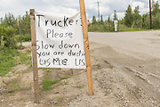 A primitive sign asking truckers to slow down on a dirt road in a rural section of Alaska outside Fairbanks, Alaska.