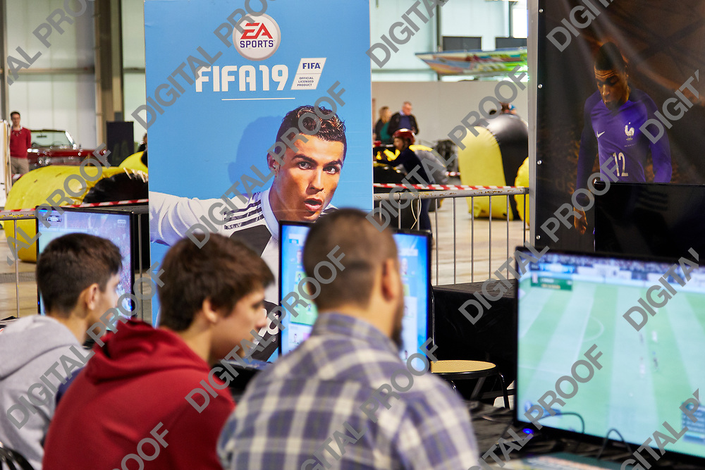 Milan, Italy - March 8 2019 Cartoomics Comic Con Visitors play FIFA 19 EA Sports game with Cristiano Ronaldo poster at the background in focus