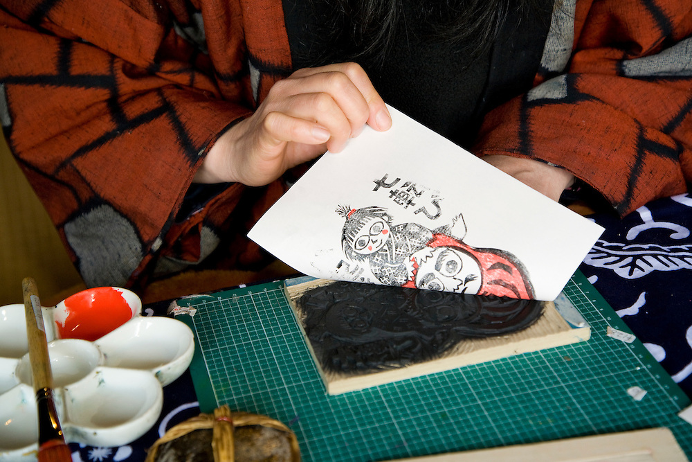 Asia, Japan, Gifu prefecture, Takayama (also known as Hida-Takayama), woman making traditional woodcut design on paper at Hida Folk Village (Hida no Sato), an open air museum illustrating the traditional architectural styles of the mountainous regions of Japan.  MR