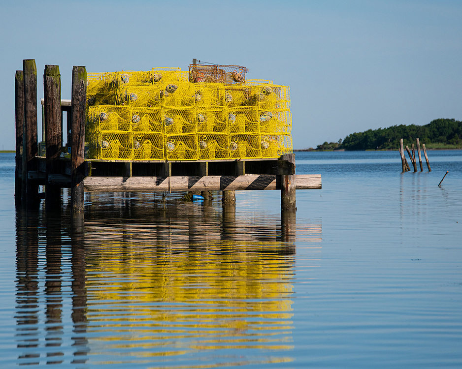 Bright yellow crab traps stacked on a pier