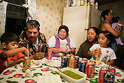 Families crowd into a neighbor's house to feast and begin celebrating the Fiesta de la Hispanidad, commemorating the coronation of the Virgen de Guadalupe as queen of the hispanic world at Hudson Valley Foie Gras in Ferndale, New York on October 11, 2008. Some of the workers and their families, practically all Mexican immigrants, live on the grounds of the factory in company provided housing; a small, isolated Mexican community flourishes in the Catskills.
