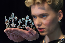 """© Licensed to London News Pictures. 19/10/2018. LONDON, UK. A model presents a diamond tiara, Hübner, circa 1912, of a fleur de lys design, with diamonds (USD350k-550k) and wears a diamond parure (USD300k-500k), both from Charles X, King of France. Preview of Sotheby's """"Royal Jewels from the Bourbon-Parma Family"""", a family descended from Louis XIV of France, the Holy Roman Emperors and from Pope Paul III, with links to the most important ruling families of Europe.  Led by a breath-taking group of jewels which once belonged to Marie Antoinette, queen of France, the collection of jewels will be offered for sale at Sotheby's in Geneva on 14 November 2018.  Photo credit: Stephen Chung/LNP"""