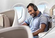 Un homme souriant en classe affaire dans un avion de la compagnie Aircalin lit et écoute de la musique au casque pendant son vol. Photothèque Aircalin