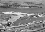 9305-B7375. Bird's-eye view of Celilo Falls. In the foreground is Seufert's Tumwater 1 fish wheel, with railcar siding. Behind it is Big island. The two rocks to the immediate right are Papoose island. ca. 1928.