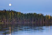A lake reflects a full moon in an Alasakan autumn landscape, Alaska