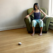 Young woman 20's something, contemplating a donut on the floor in living room.