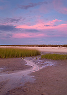 A sunset sky over the low-tide edge of Wing Island in Brewster.