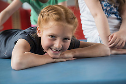 Girl lying on exercise mat in large gym of school, Bavaria, Munich, Germany