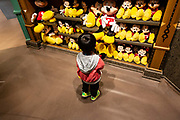A child holds a Mickey Mouse stuffed toy inside a World of Disney store at the Disneytown retail area of Walt Disney Co.s Disneyland Resort in Shanghai, China, on Saturday, May 7, 2016. The $5.5 billion Shanghai Disneyland is one  of the most profitable Disney ventures in the world and the first theme park on mainland China.