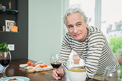 Portrait of mature man holding wine glass in kitchen, smiling