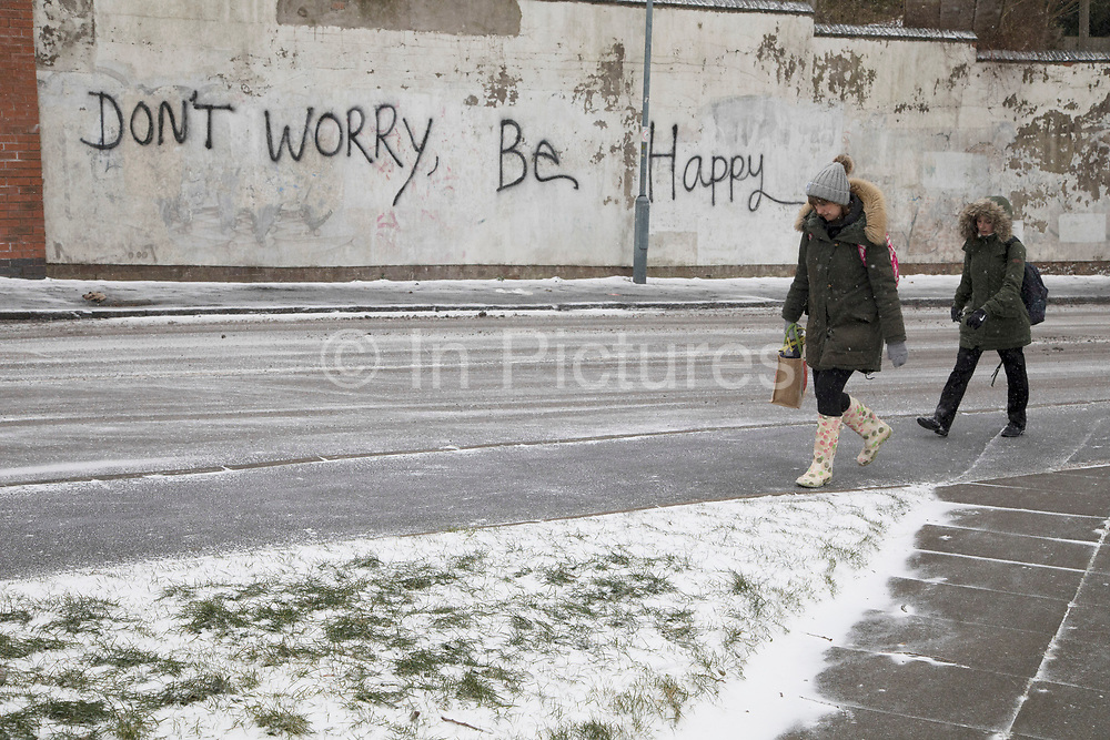 Don't worry be happy graffiti during freezing weather, dubbed 'The Beast from the East' due to the sub zero cold temperature winds coming in from Siberia, descends on Kings Heath High Street on 1st March 2018 in Birmingham, United Kingdom.