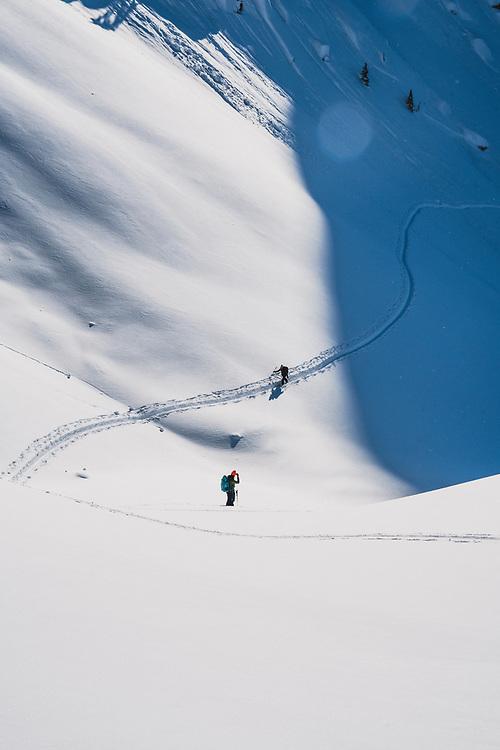 Into the light. Matt Kennedy spots Ali Vagnini while skinning up the Fondue Bowl, Meadow Hut, Esplanade Range, BC.