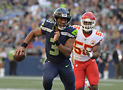 Aug 25, 2017; Seattle, WA, USA;  Seattle Seahawks quarterback Russell Wilson (3) is pursued by Kansas City Chiefs outside linebacker Dee Ford (55) during a NFL football game at CenturyLink Field. The Seahawks defeated the Chiefs 26-13.