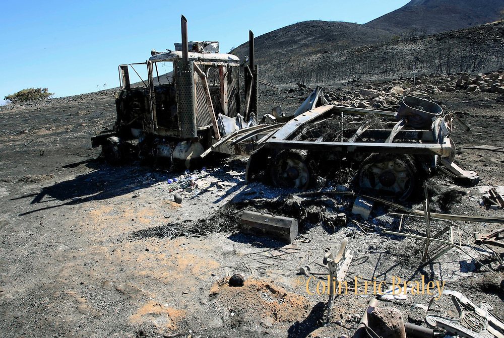 Burned out truck and thousands of acres of charred brush are all that remains after a wildfire destroyed numerous homes and forced the evacuation of more than 1,600 homes Monday, Sept. 20, 2010, in Herriman, Utah. The blaze was started by live-fire exercises at Camp Williams, a Army National Guard base southwest of Salt Lake City.. (AP Photo/Colin E. Braley)