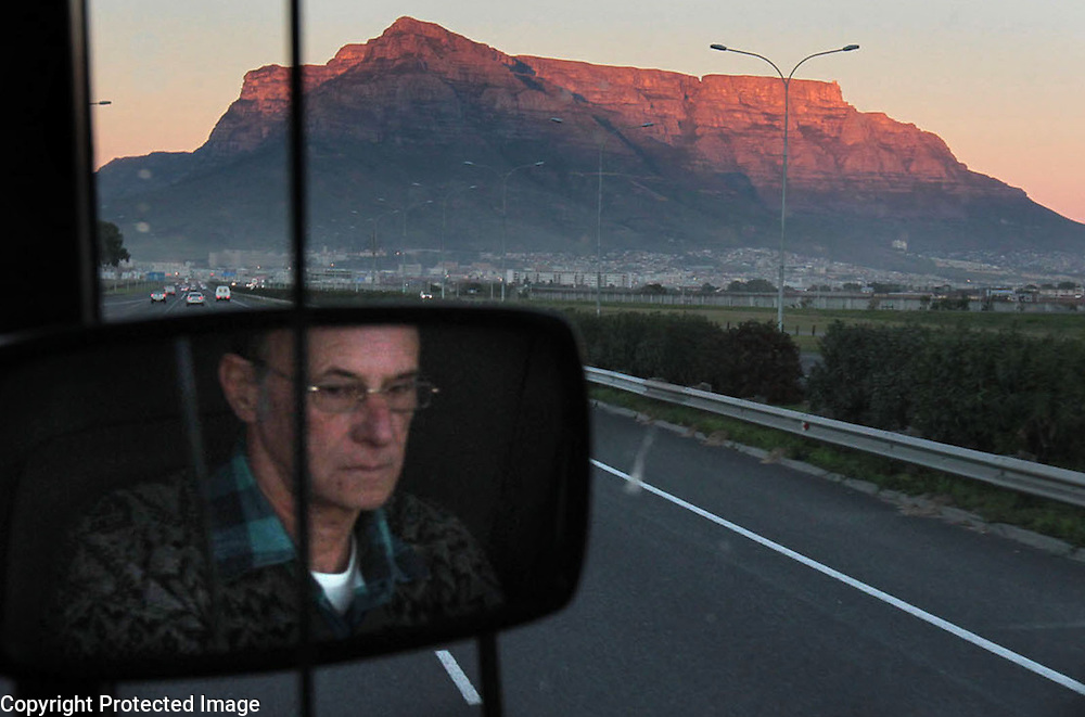 The sunrise lights Cape Town's Table Mountain as a bus driver steers his vehicle toward the city center.<br /> Photo by Shmuel Thaler <br /> shmuel_thaler@yahoo.com www.shmuelthaler.com