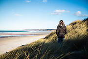 Woman walking through the sand dunes and looking out over the beach at Le Braye, St Ouen, Jersey, Channel Islands