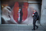 Large red lipstick covered lips hoarding on Bond Street, London, UK. Another of the exclusive shops in the area under refurbishment. The face, which is a close up of someone who has photocopied their features makes scale of passers by look small.