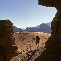A rock climber hikes between remote desert cliffs in Rakabat Siq (canyon), on (Mount) Jebel Um Ishrin, Wadi Rum, Jordan.