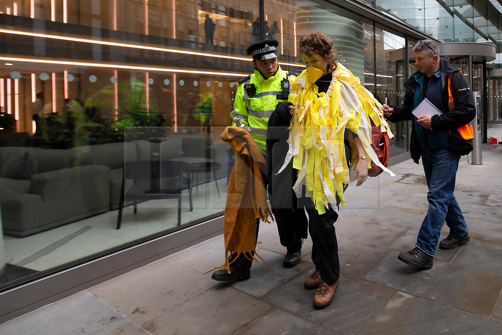 © Licensed to London News Pictures. 14/10/2019. London, UK. An Extinction Rebellion protester dressed as a canary is removed from The Walkie Talkie building . Protesters are today targeting the financial district.  Photo credit: George Cracknell Wright/LNP