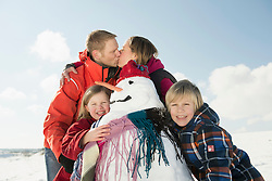 Girl and boy standing with snowman, parents kissing in background, Bavaria, Germany