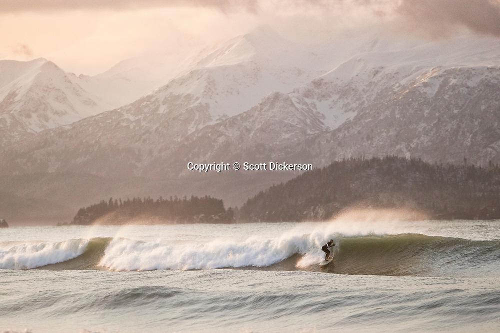 Don 'IceMan' McNamara surfing a winter swell at sunrise on Kachemak Bay, Alaska. The Kenai Mountains rise in the background.