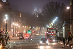 © Licensed to London News Pictures. 30/11/2020. London, UK. Light traffic on Whitehall during a foggy morning in central London. Parts of the UK are experiencing heavy fog and low temperatures. Photo credit: George Cracknell Wright/LNP
