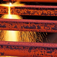 USA, Washington, Seattle, Sparks fly from acetylene torch cutting bars of red hot steel at Birmingham Steel Plant