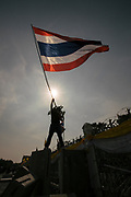 An anti-Government protester standing on top of concrete barriers and waving the Thai national flag in front of Government House in Bangkok. Thailand.