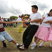 Johnathan Garcia, 8, left, appears to take on Alfredo Pena, 8, Brianna Arelano, 9, and Ashley Trevino, 8, all alone in a game of tug-of-war during a celebration for 50th year of Zavala Elementary School in McAllen. Garcia had help from the rest of his 2nd grade class behind him on the rope, but they lost the round anyway. <br /> Nathan Lambrecht/The Monitor