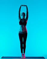 one caucasian woman exercising yoga exercices Tadasana mountain pose in silhouette studio isolated on blue background