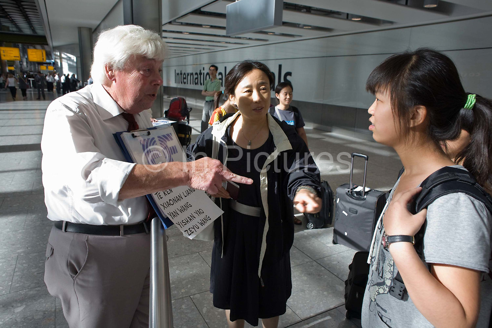 """A greeting driver attempts to identify one of his passengers from a group of non-English-speaking young people who have just arrived off a flight from Beijing. In the hectic international arrivals concourse of Heathrow's Terminal 5, the man hold up a name board to attract the attention of those Chinese nationals who are new students at a Bournemouth language college called Education First (EF), based on England's south coast. With the help of a chaperone, the man points to a young girl in the hope she might be on his list. Neither speak each other's mother tongue and the language barrier is difficult to overcome. From writer Alain de Botton's book project """"A Week at the Airport: A Heathrow Diary"""" (2009)."""
