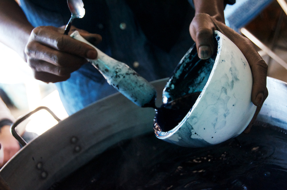Aboubakar Fofana natural indigo paste into an indigo vat at a Indigo dye and bogolan workshop held with Aboubakar Fofana in Johannesburg, South Africa
