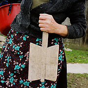 A Romanian peasant wearing a flowery apron holds a wooden washboard and a bowl of clothes for washing in the river, Botiza, Maramures, Romania.