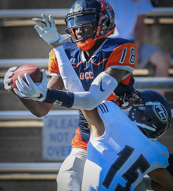 Orange Coast Pirate wide receiver James Rutledge (18) completes the reception around Fullerton Hornet defensive back Andrae Pierman (15) during the game played in Costa Mesa, California, Saturday, Nov 5, 2016. Photo By: Bryan Woolston, Sports Shooter Academy