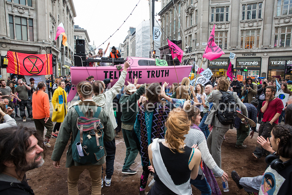 London, UK. 16th April 2019. Climate change activists from Extinction Rebellion dance at Oxford Circus alongside the Ship of Truth on the second day of International Rebellion activities to call on the British government to take urgent action to combat climate change.