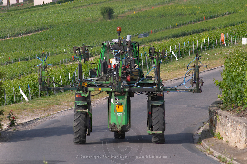 A green vineyard tractor for spraying the vines on a road going back to the winery. It is equipped to spray five 5 rows at a time, the village of Hautvillers in Vallee de la Marne, Champagne, Marne, Ardennes, France