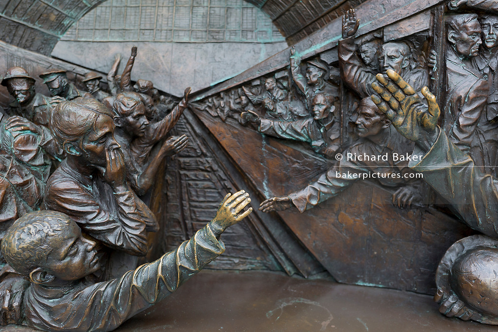 As the UK government urged that all Britons should avoid non-essential travel abroad in order to combat the Coronavirus pandemic in Britain and when physical contact is discouraged, a detail showing families saying farewell to departing WW1 troops at a station platform, found on the lower base of the statue entitled The Meeting Place by British artist Paul Day, on 17th March 2020, in London, England. The Meeting Place is a 9-metre high, 20-tonne bronze statue that stands at the south end of the upper level of St Pancras evoking the romance of travel through the depiction of a couple locked in an amorous embrace. It's cost is reported to be £1 million. St. Pancras is the London terminus for Eurostar services to mainland Europe.