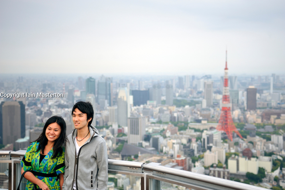 Young couple posing for photograph with Tokyo Tower to rear in central Tokyo Japan