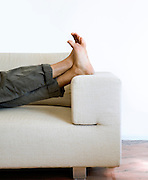 Detail of the feet of man lying on the sofa
