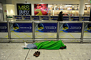 A passenger sleeps at Heathrow Airport, Terminal 3 as airports across Europe begin to get passengers home after being closed because of the Volcano in Iceland.
