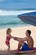 A little girl tugs on her father's hands to get him to go in the water, on the beach in Hawaii