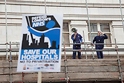 London, UK. Saturday 18th May 2013. Protestors dressed as surgeons shouted from high up on some scaffolding during demonstration against NHS reform and proposed funding cuts for services within the National Health Service.