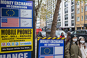 Passers-by wearing face coverings walk past signs for Commission Free money exchange and mobile phone repairs on Charing Cross Road, on 30th October 2020, in London, England.