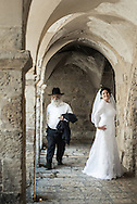 An orthodox Jew finds himself in the middle of a wedding portrait session at King David's Tomb site on Mount Zion, in Jerusalem.