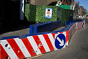Man made barrier made of concrete and painted with red and white stripes and hoarding made to look like a large hedge of leaves, outside a construction site at Smithfields in London, UK.