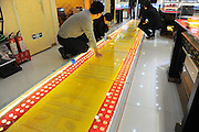 TAIYUAN, CHINA - NOVEMBER 19: (CHINA OUT) <br /> <br /> Twelve-meter-long Golden Road <br /> <br /> Staff pave twelve-meter-long golden road on November 19, 2014 in Taiyuan, Shanxi province of China. A jewelry shop paved a twelve-meter-long road with gold coins during its upcoming shop celebration at the shopping mall to attract consumers.<br /> ©Exclusivepix